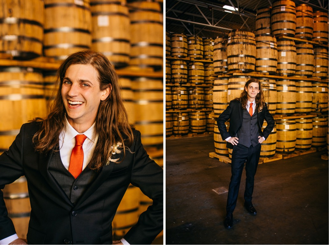 groom laughs near stacks of barrels at Chattanooga Whiskey Distillery wedding