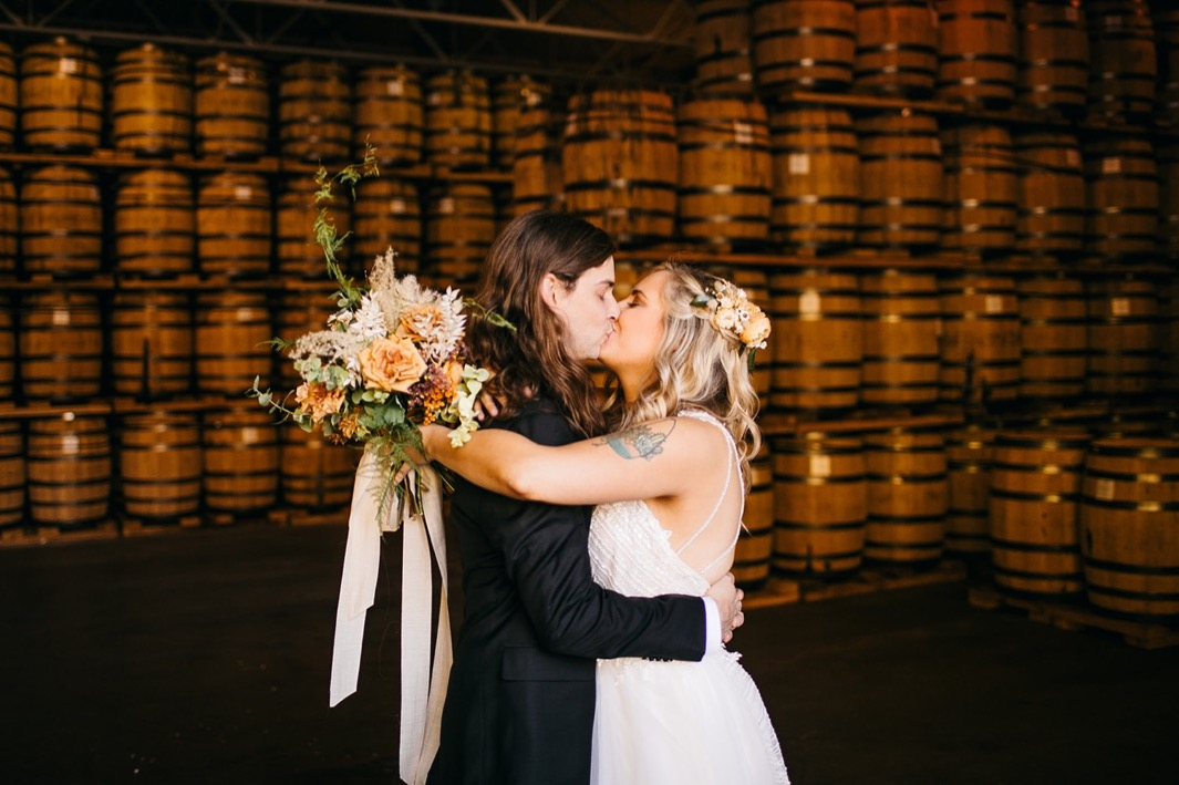 bride and groom kiss in front of stacks of barrels at their Chattanooga Whiskey Distillery wedding