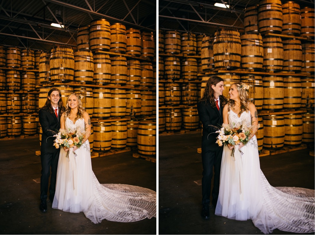 bride and groom stand in front of stacks of barrels at their Chattanooga Whiskey Distillery wedding