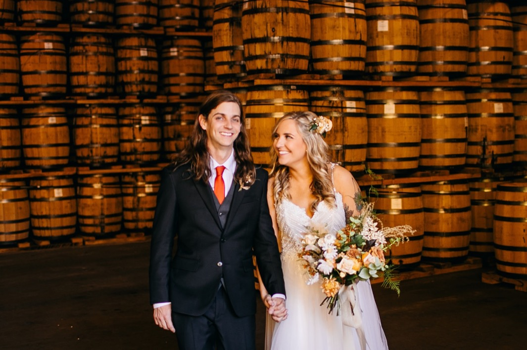 bride and groom smile at each other in front of stacks of barrels at their Chattanooga Whiskey Distillery wedding