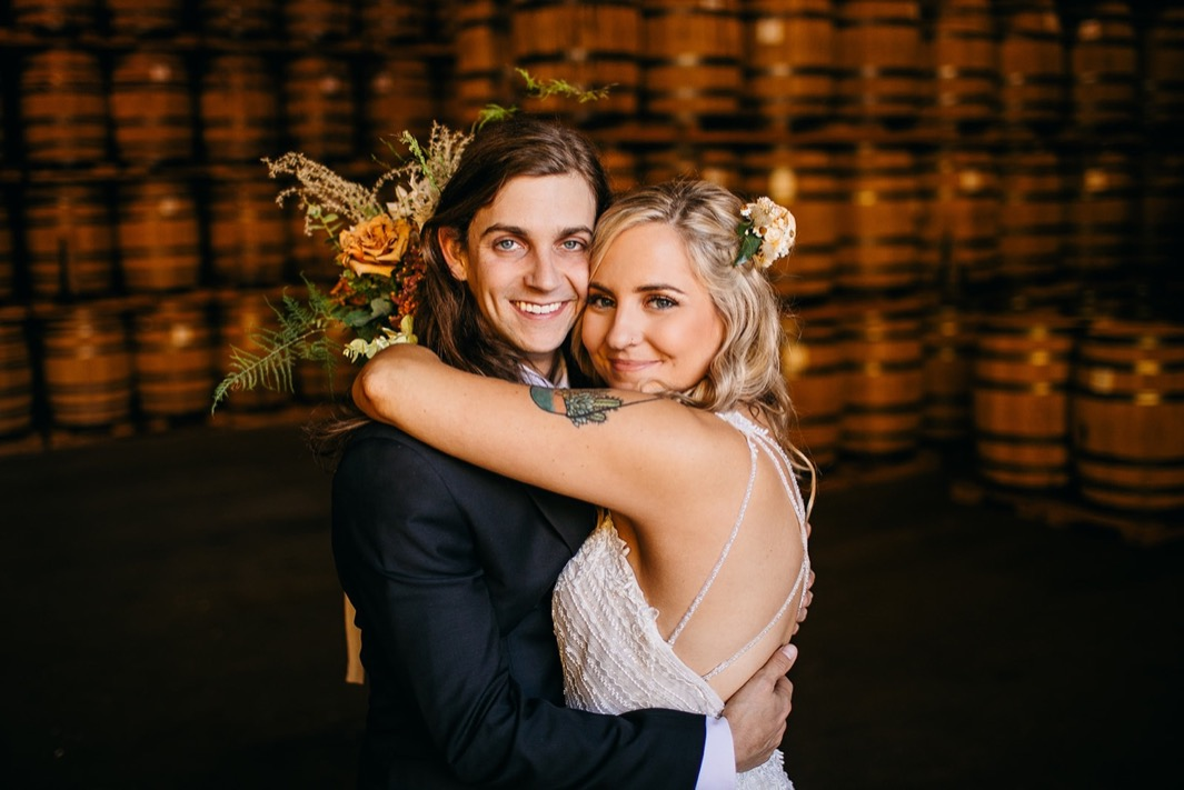 bride and groom hug each other in front of stacks of barrels at their Chattanooga Whiskey Distillery wedding