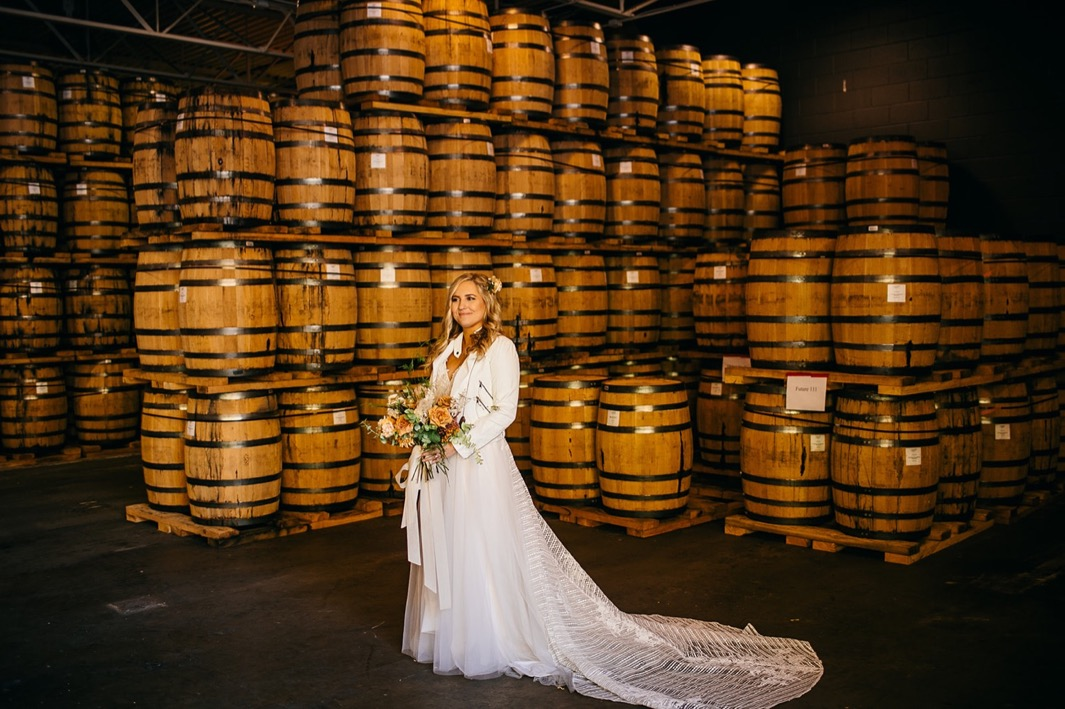 bride in her gown holds Southerly Flower Farm bouquet in front of stacks of barrels at Chattanooga Whiskey Distillery wedding