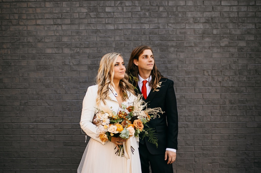 bride in white jacket and gown holding Southerly Flower Farm bouquet stands with groom outside Chattanooga Whiskey Distillery