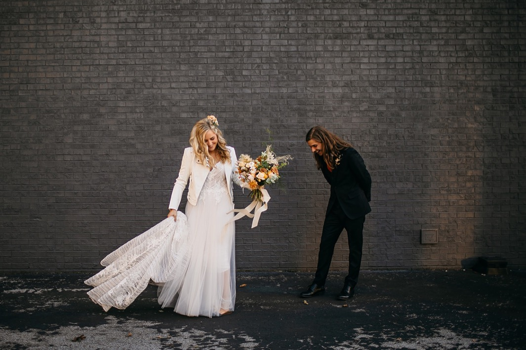 bride in wedding gown and jacket laughs with groom outside against dark painted brick wall of Chattanooga Whiskey Distillery