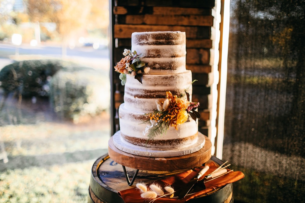 multi-tiered naked wedding cake sits on top of Chattanooga Whiskey barrel