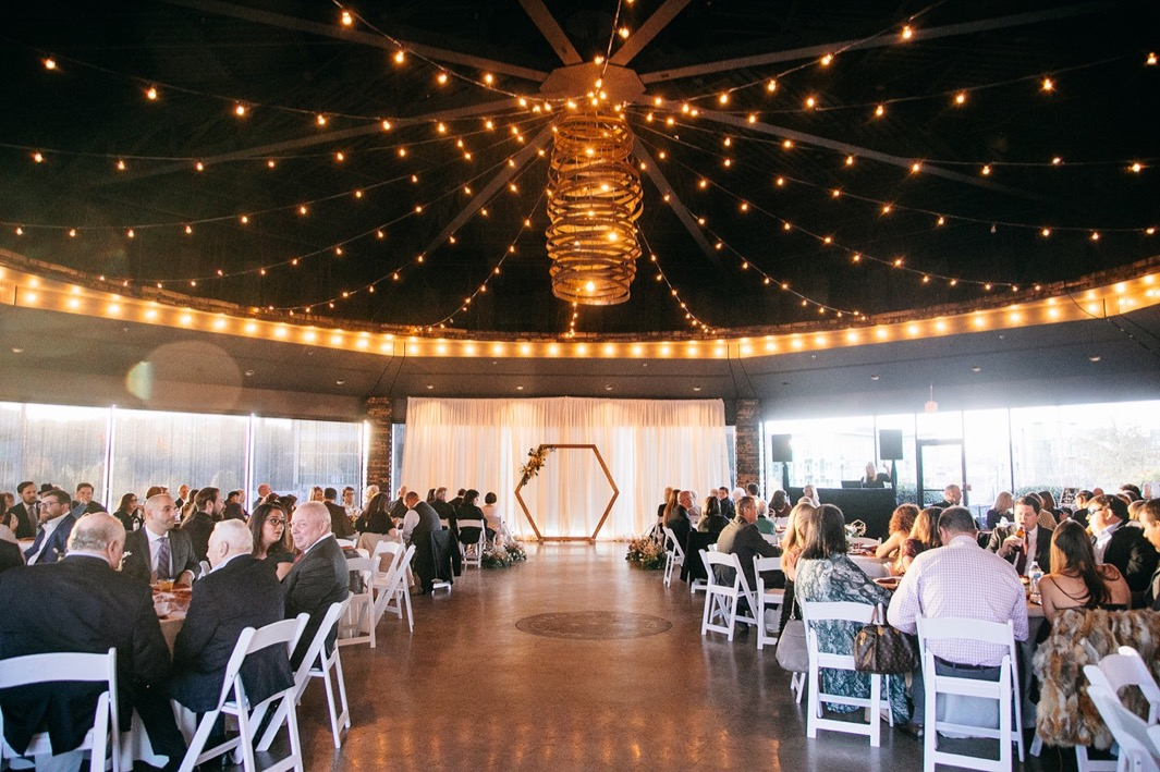 interior of Chattanooga Whiskey Distillery wedding with guests seated at round tables and wedding arch at front of room