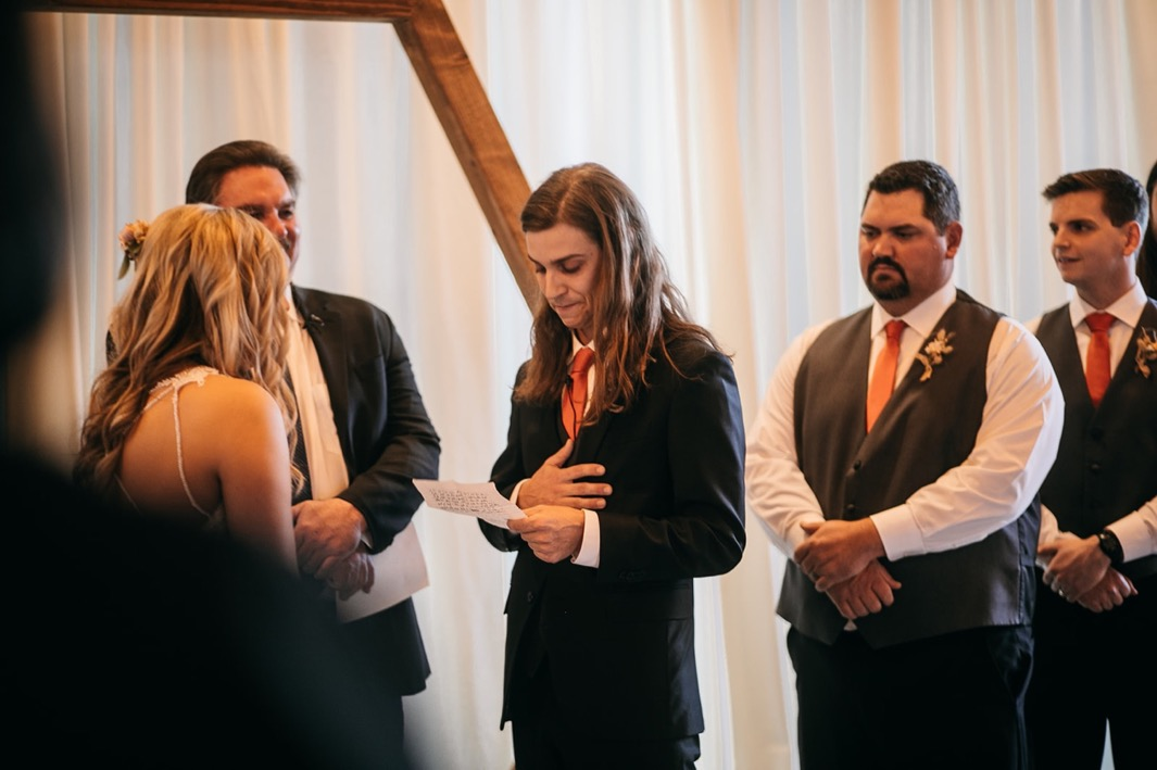 groom holds hand over his heart while he reads his vows to the bride