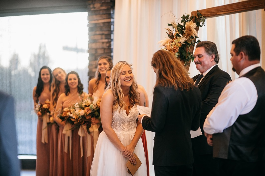 bride laughs during groom reading wedding vows to her