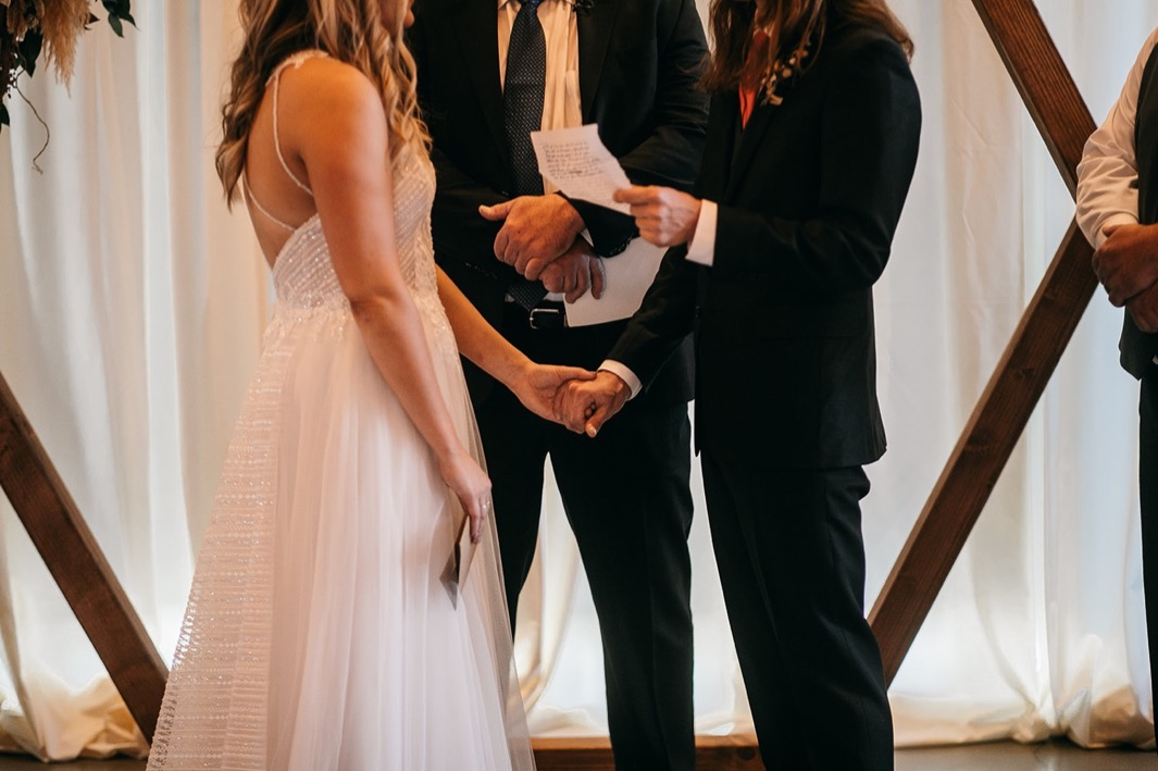 groom holds bride's hand while he reads vows during their Chattanooga Whiskey Distillery wedding