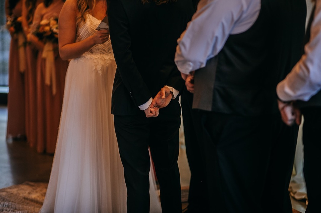 groom holds his hands behind his back while bride reads her vows to him