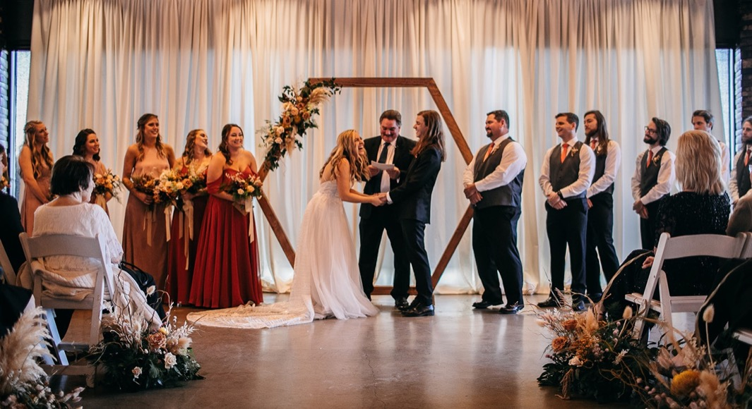 bride and groom laugh with wedding party while officiant reads wedding ceremony at Chattanooga Whiskey Distillery wedding