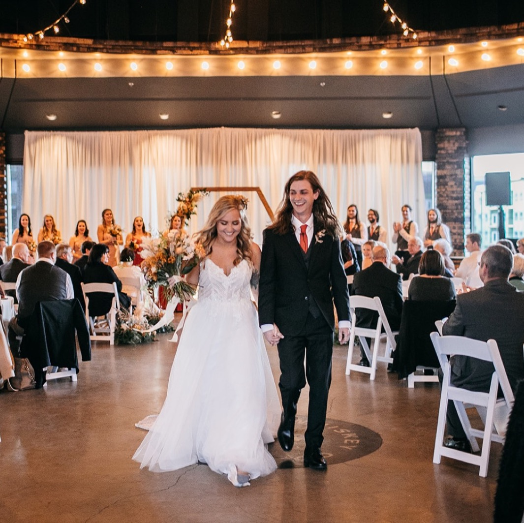 bride and groom walk down the aisle of their Chattanooga Whiskey Distillery wedding ceremony