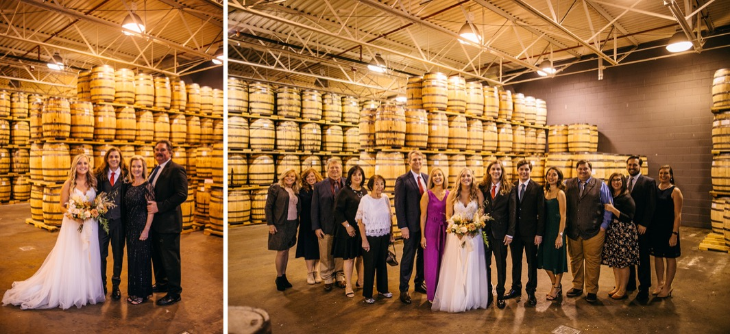 bride and groom pose with family members in front of whiskey barrels at Chattanooga Wiskey