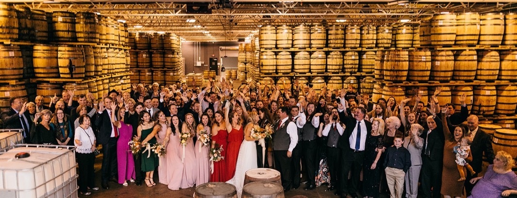 wedding party and guests pose for a large group photo between stacks of barrels and Chattanooga Whiskey Distillery wedding