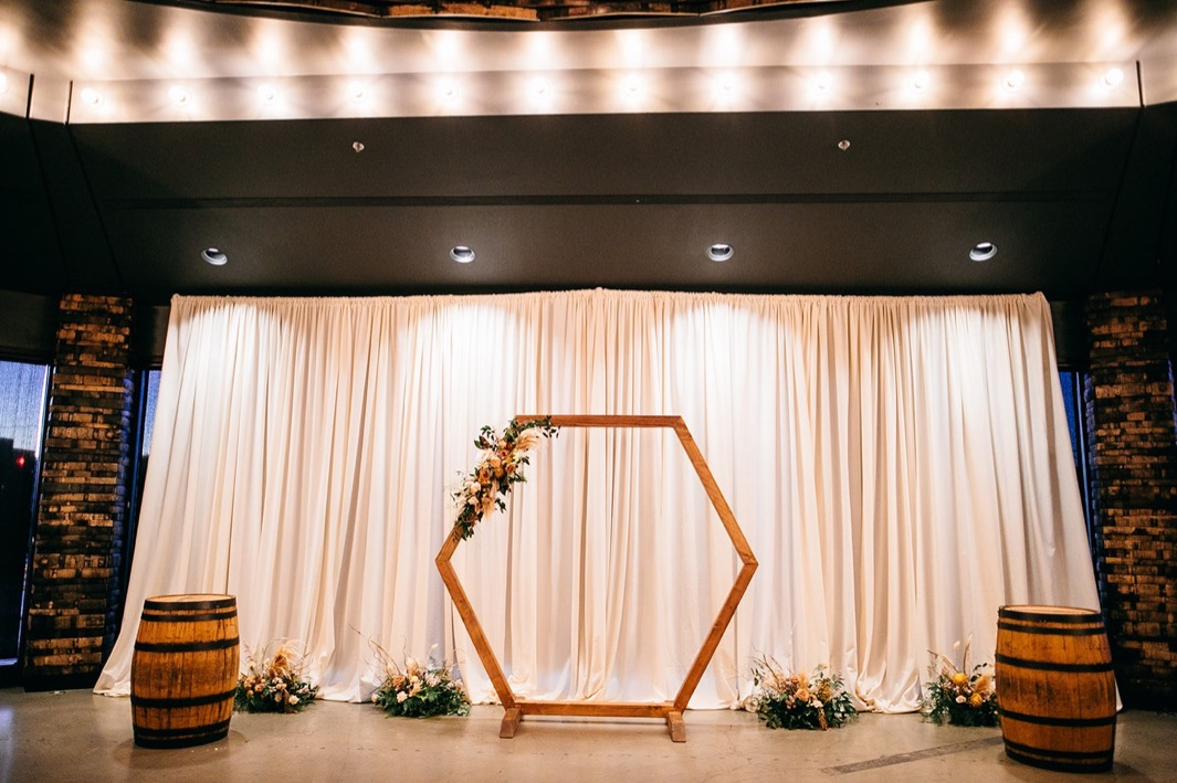 ceremony space set with geometric arch and Southerly Flower Farm arrangements in front of tall white curtain