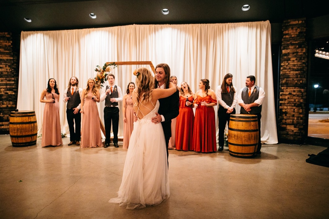 bride and groom share first dance at their Chattanooga Whiskey Distillery wedding while wedding party watches