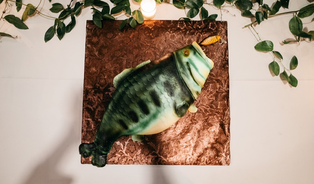 fake plastic fish sits near greenery and tea light on a table