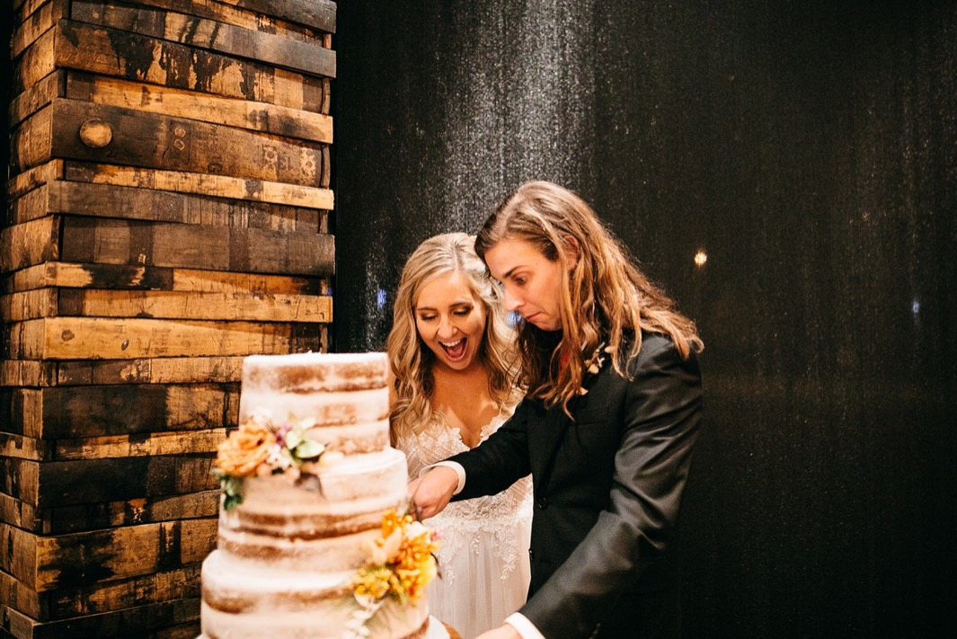 bride and groom cut into multi-tier naked wedding cake