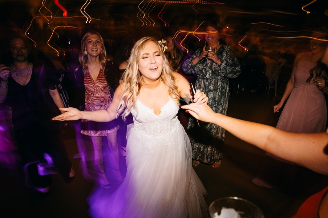 wedding guests dance around bride in a dark room