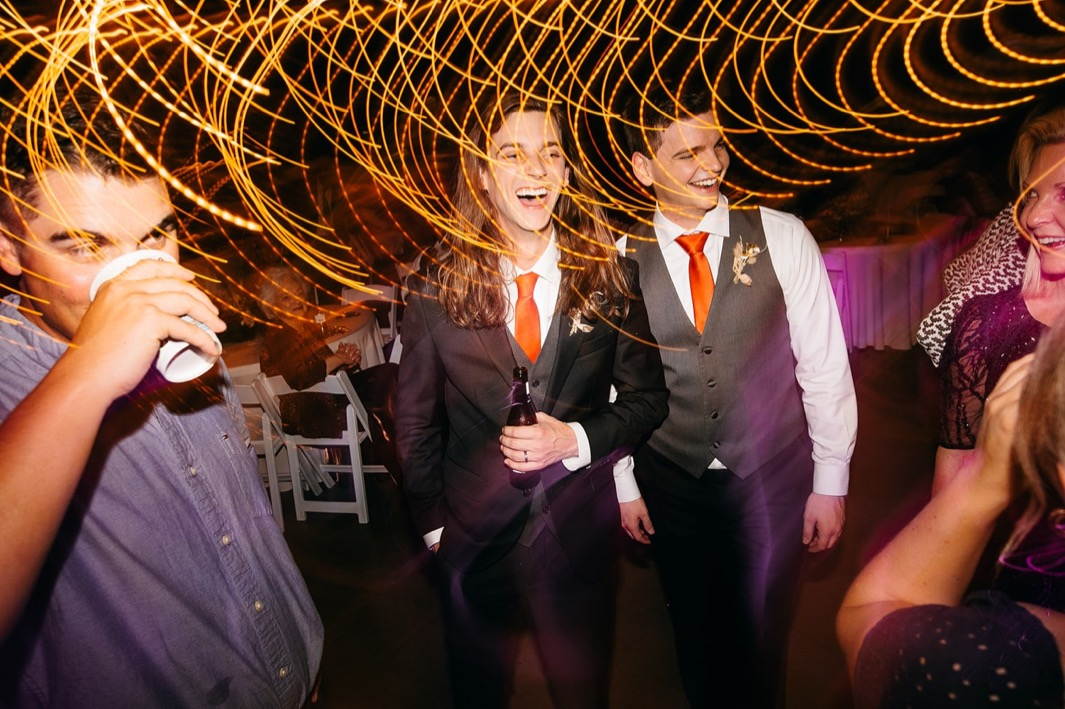 groom laughs with groomsmen and guests