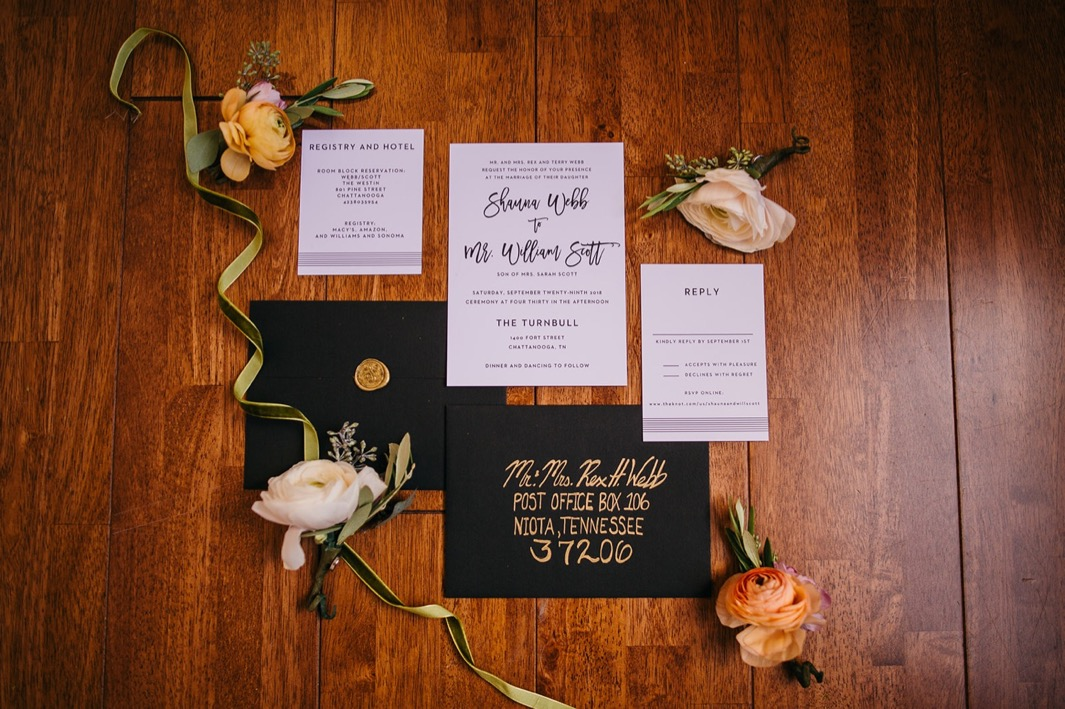 A flatlay of an invitation suite for a wedding at the Turnbull building