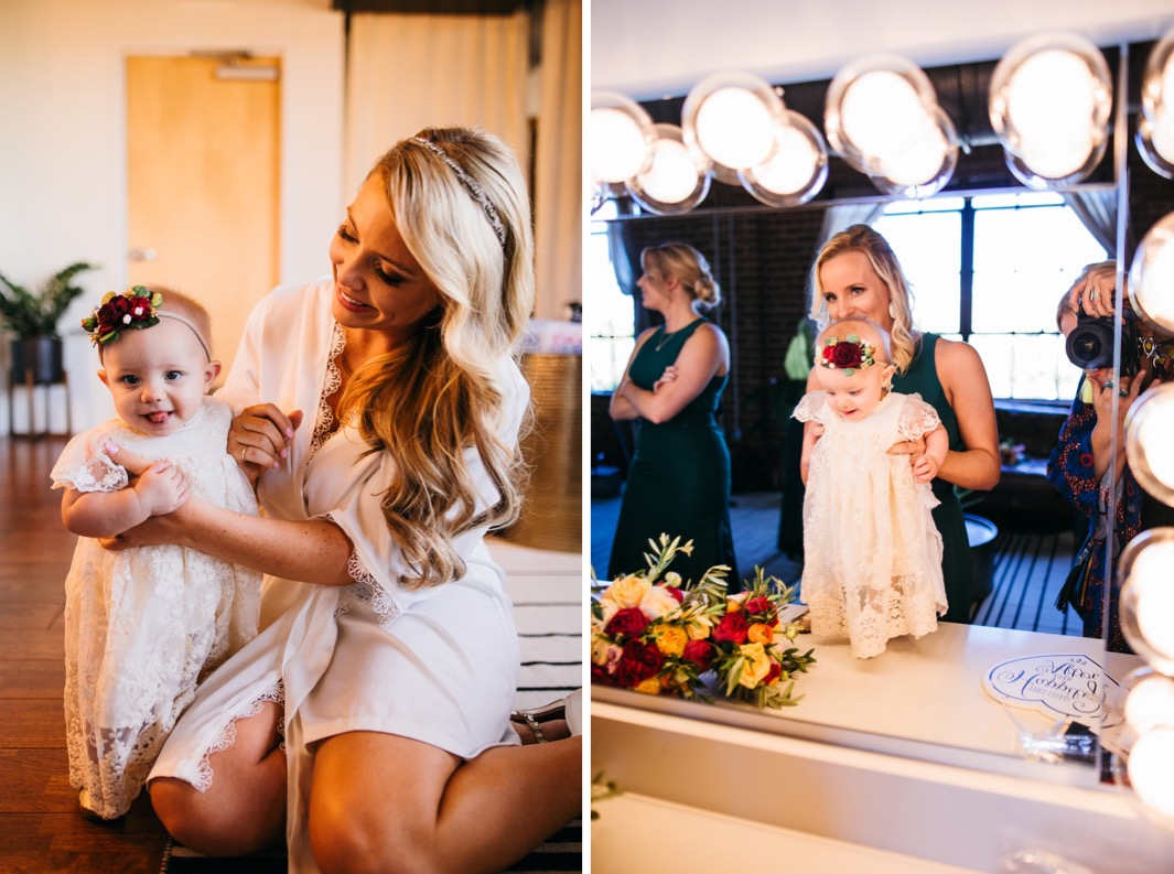 Bride sits on the floor and holds the flower girl for a photo before her wedding at the Turnbull building. Bridesmaids stand flower girl up on their beauty table