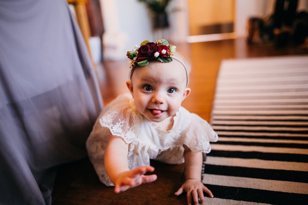 Flower girl is wearing a white lace dress with a red rose headband for the wedding at the Turnbull building