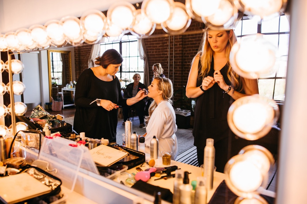 Makeup artist is putting lipstick on the bride for her Turnbull building wedding