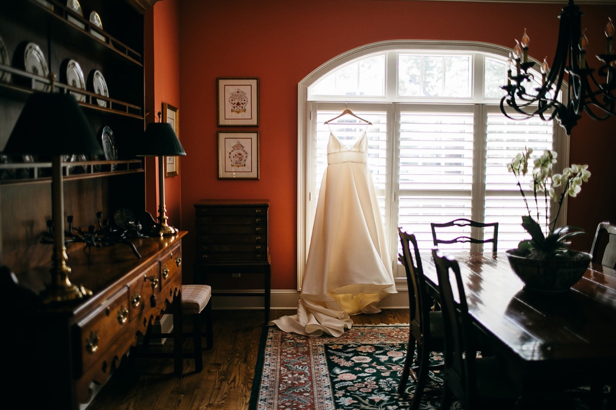 wedding dress hangs in a large window with train puddling on wood floor.