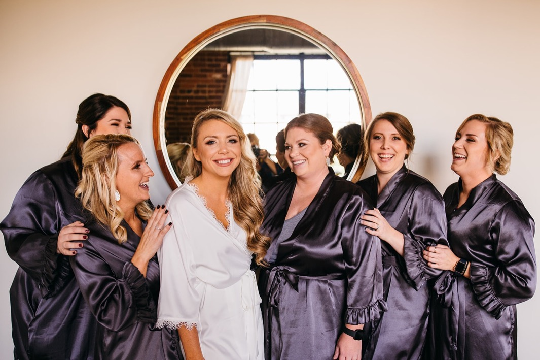 Bride and bridesmaids laugh while taking a photo in their robes before the Turnbull building wedding