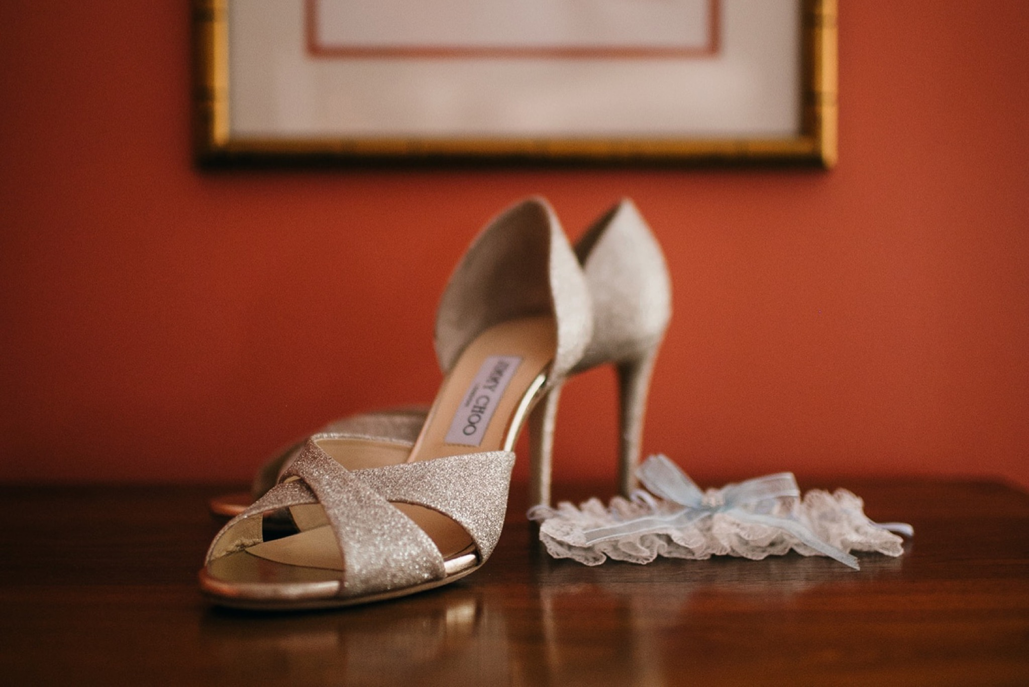 sparkly high heels sit on wooden surface next to lace and ribbon garter