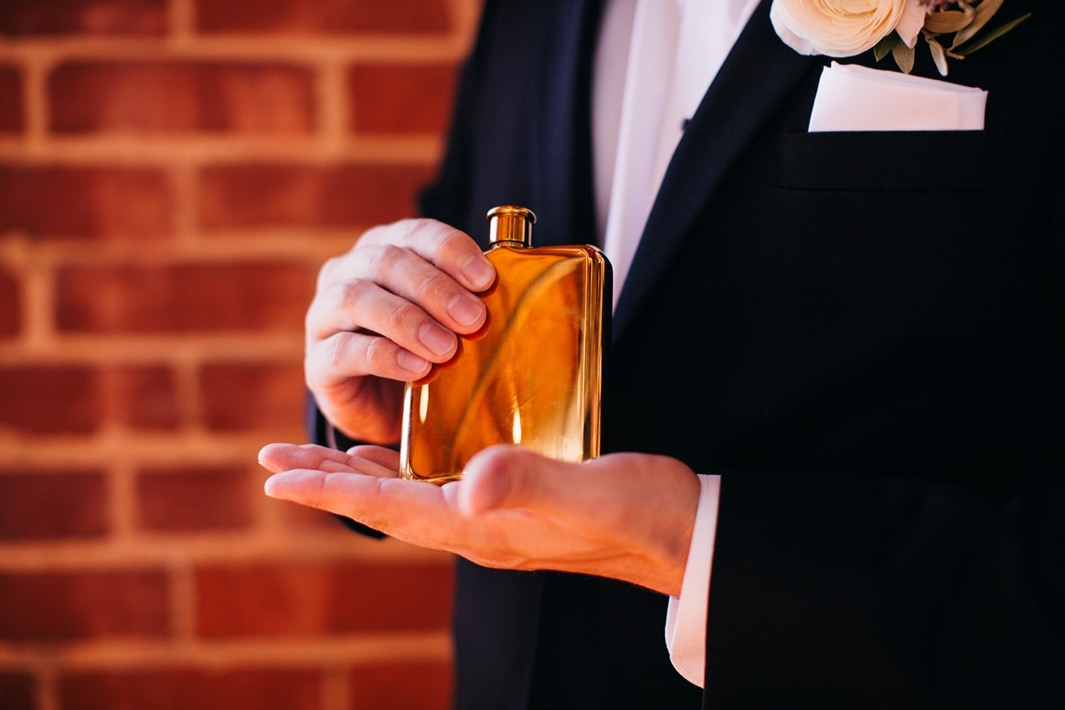 Groom holds his gold flask during a closeup shot.
