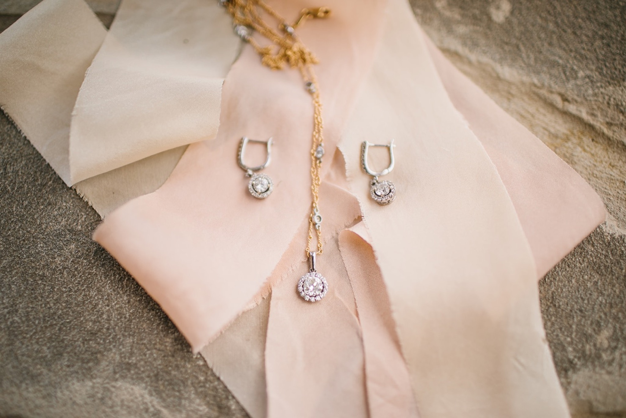 diamond earrings and necklace rest on pale pink strip of fabric
