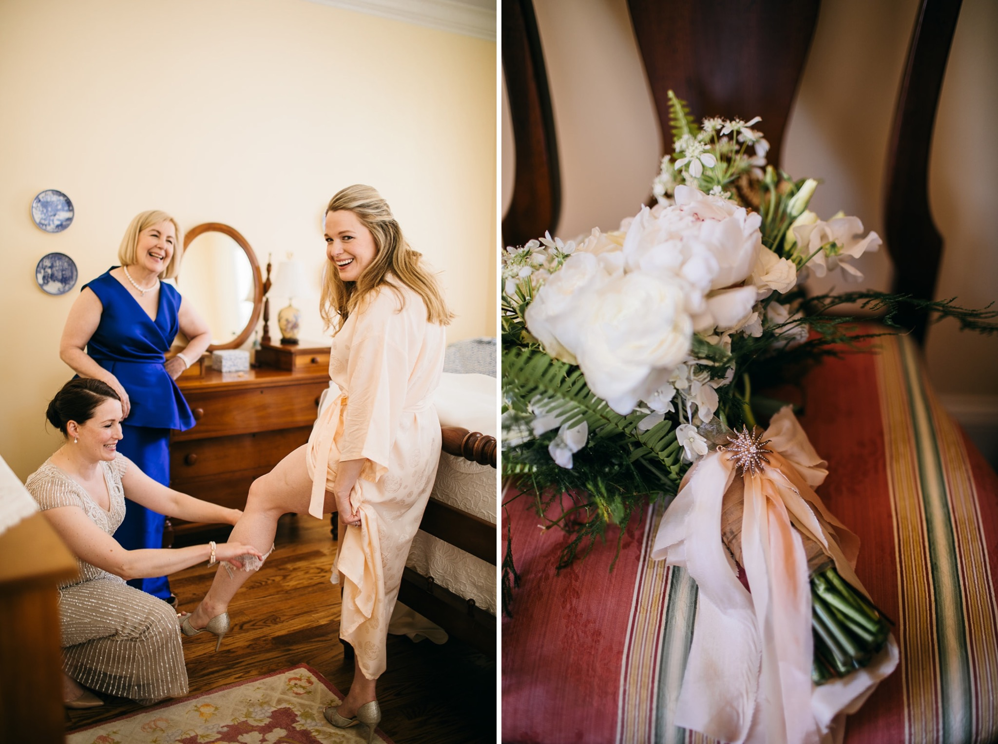 matron of honor helps put garter around bride's calf while mother of bride watches and laughs