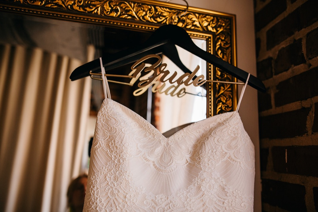 Close up shot of the brides wedding dress with a sweetheart neckline handing on her bride hanger.
