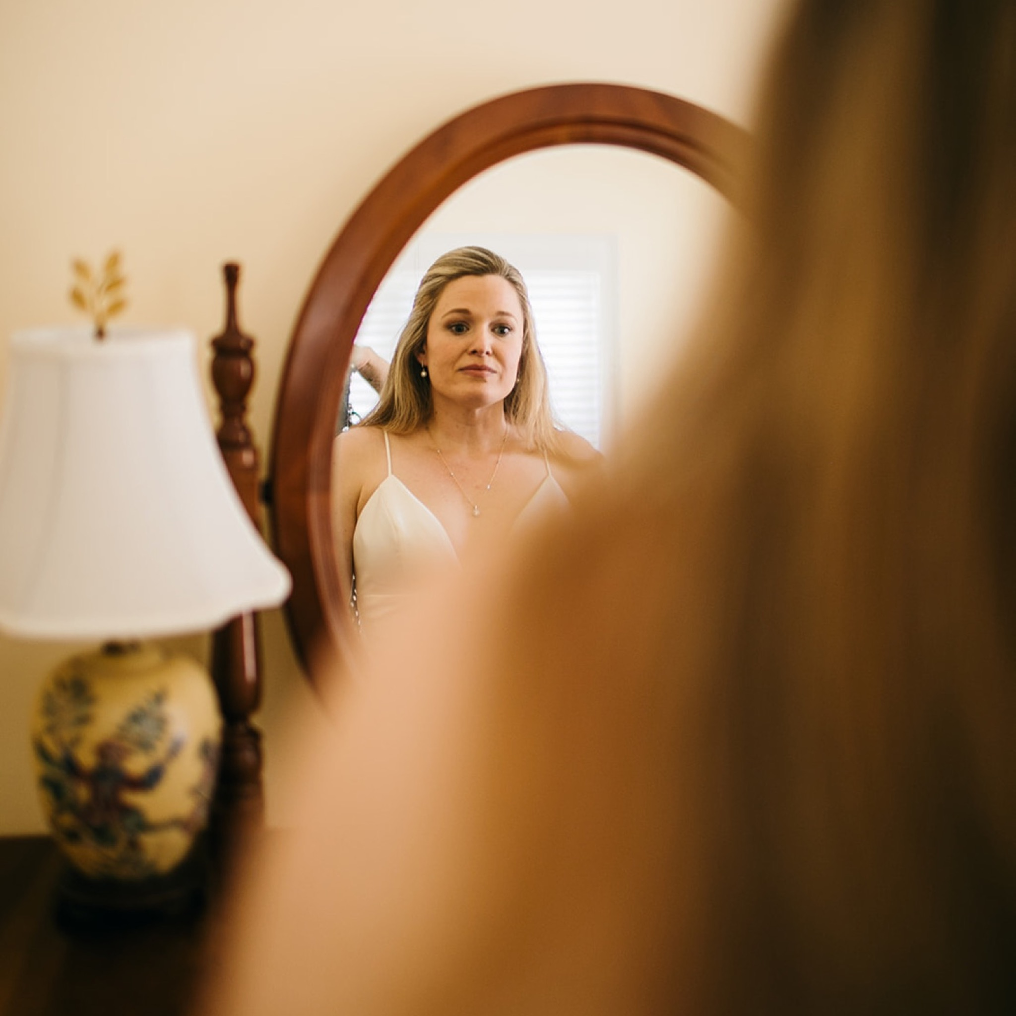 bride stands before oval mirror to see her reflection