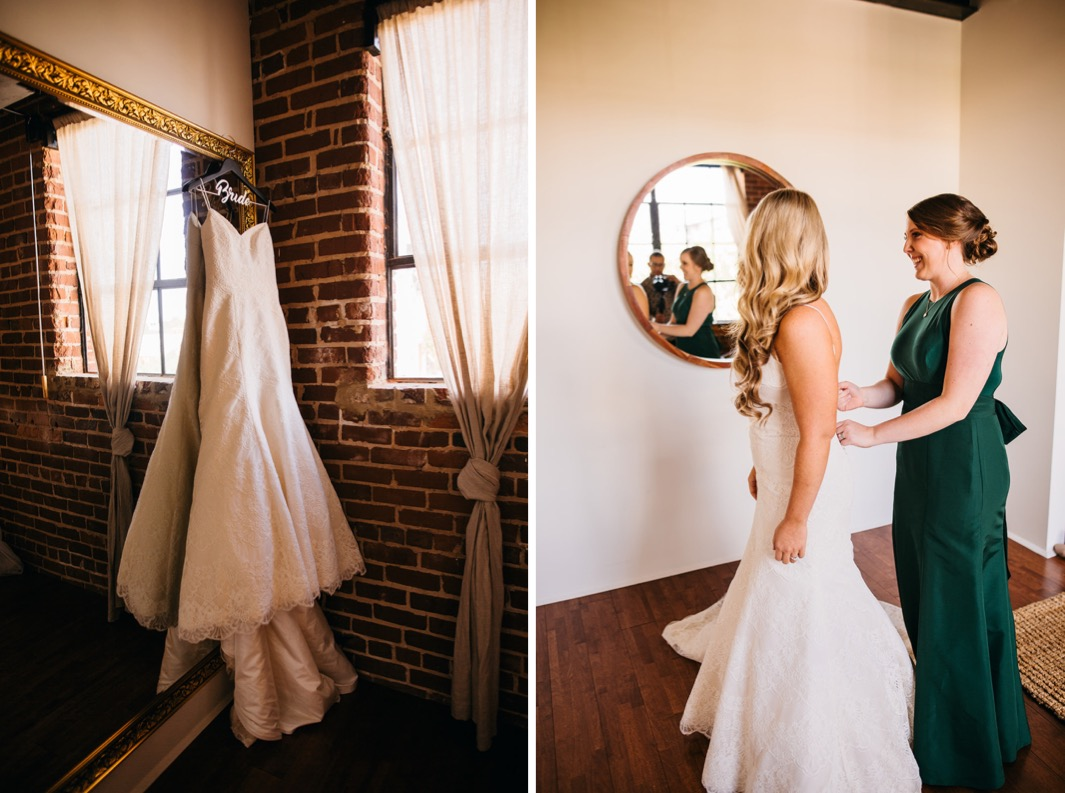Brides wedding dress hangs against a gold trimmed mirror. Bridesmaid is fixing the brides fitted wedding dress as she gets ready for her wedding at the Turnbull building.