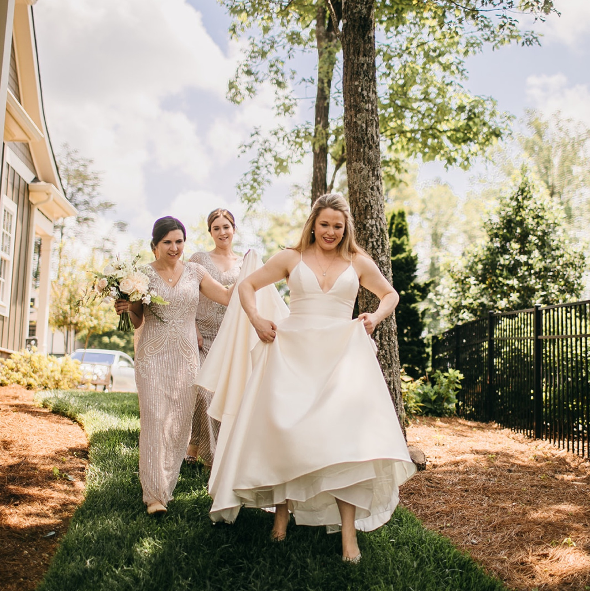 bride holds up her dress as she walks through green grass; bridesmaids carry her train behind her.
