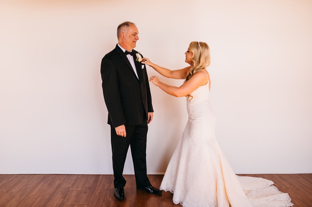 Bride fixes fathers boutonniere during her dress reveal at her Turnbull building wedding.