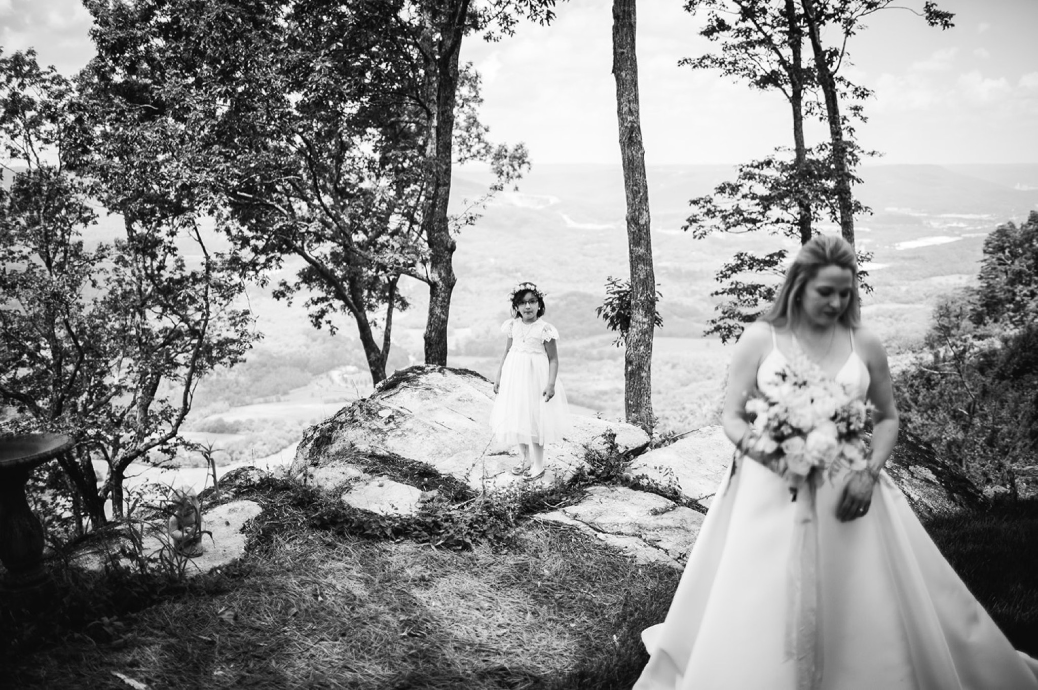 small girl stands on a large rock at the edge of cliffside overlook while bride holds bouquet of flowers in front of her