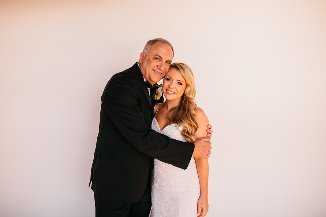 Brides father hugs her tight at her Turnbull building wedding.
