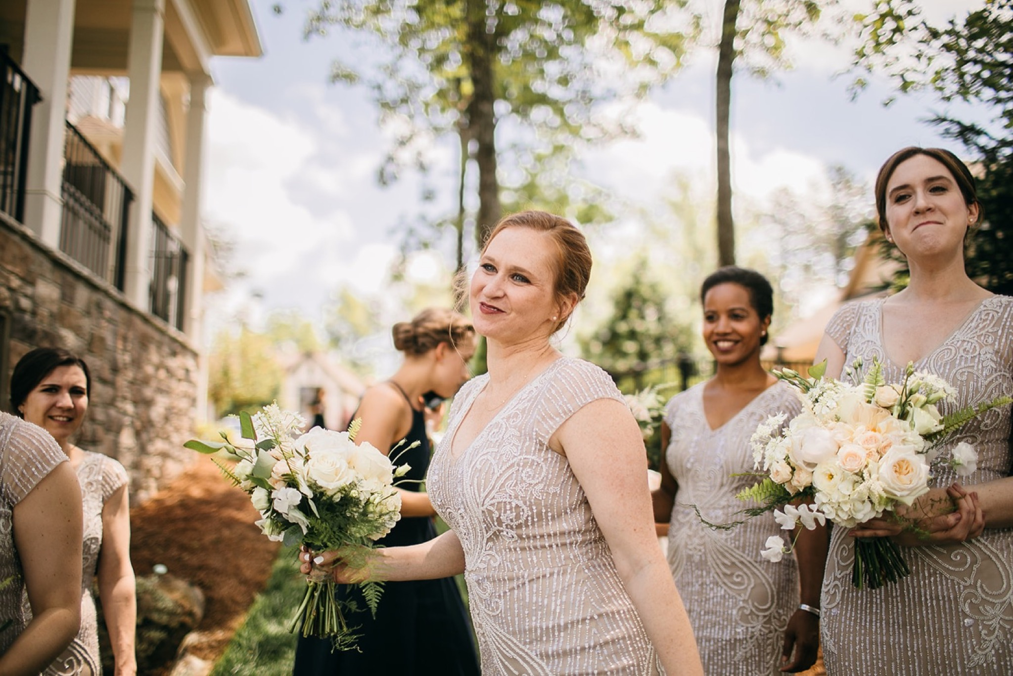 bridesmaids in sequin-decorated dresses hold bouquets of white and light peach flowers