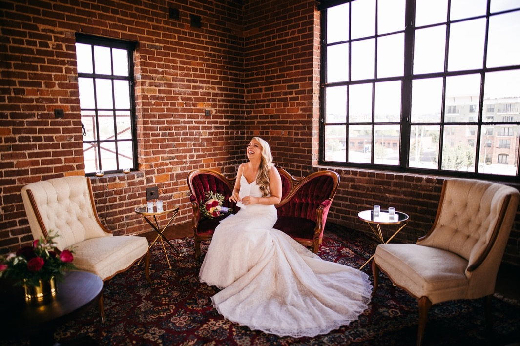 Bride laughs as she sits on a red velvet chaise at her wedding at the Turnbull building.