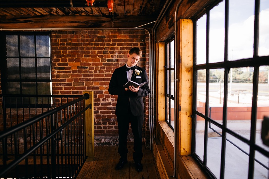 Groom reads through a journal inside the Turnbull building at his wedding.