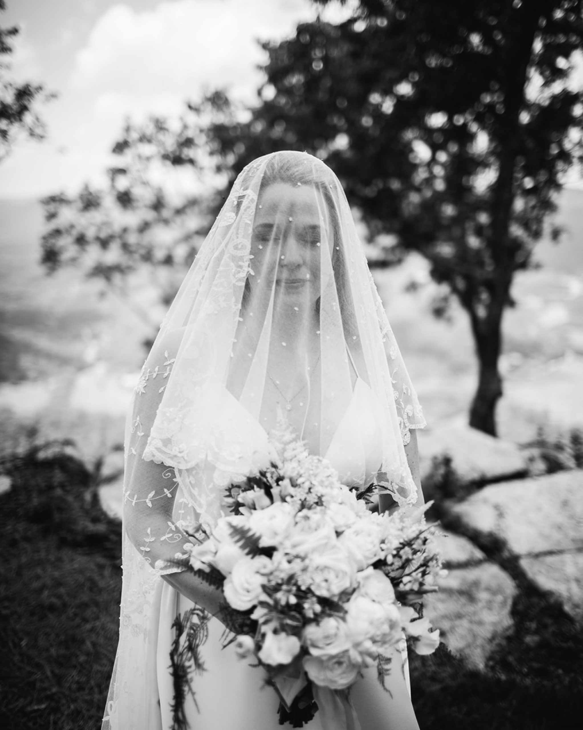 bride holds her large bouquet of white flowers with her veil over her face