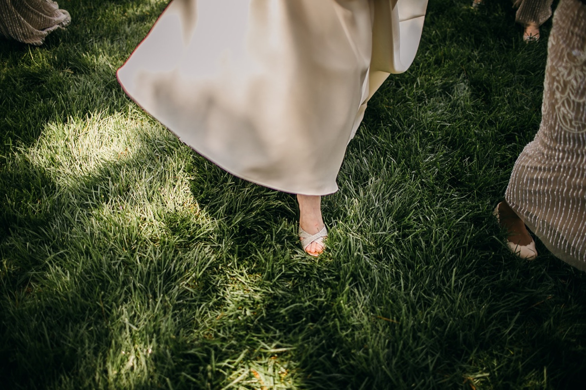 bride steps into lush green grass with her sparkly heels