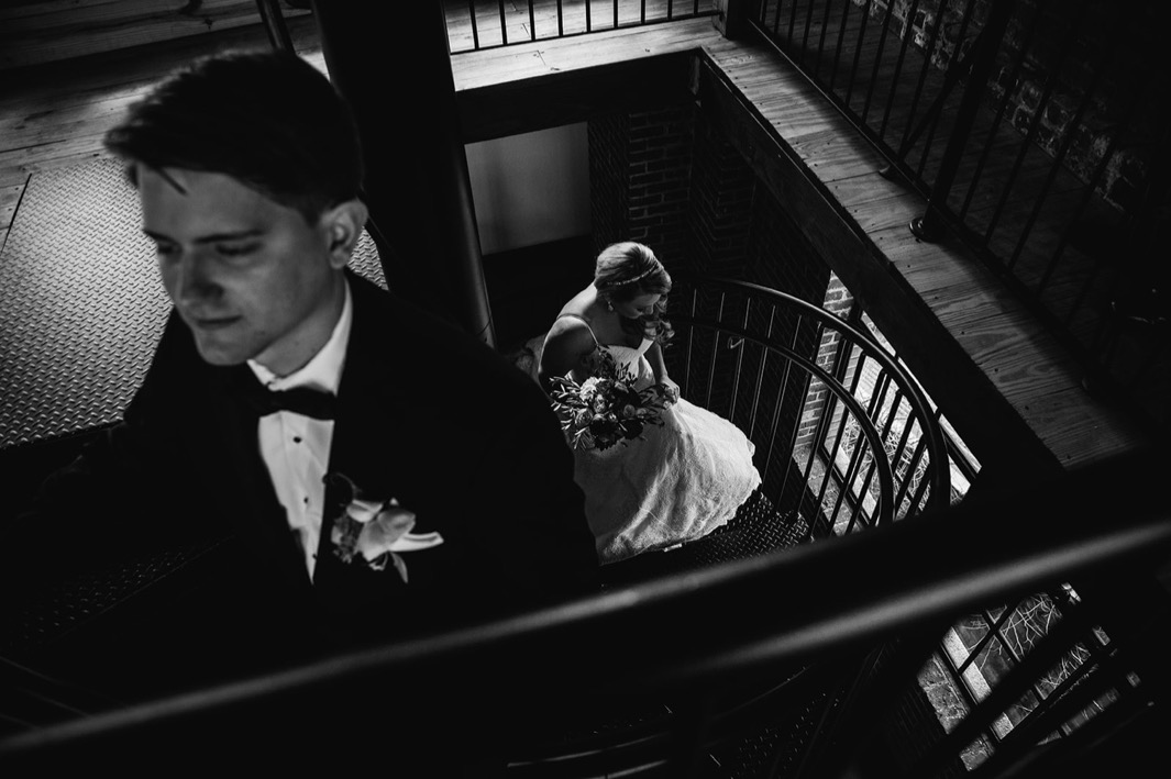Bride walks up the spiral staircase towards the groom at their wedding in the Turnbull building.