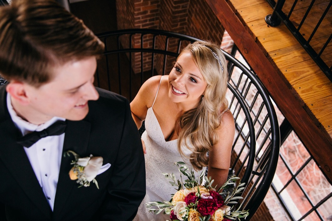 Bride smiles at groom as he turns around for a first look during their wedding at the Turnbull building.