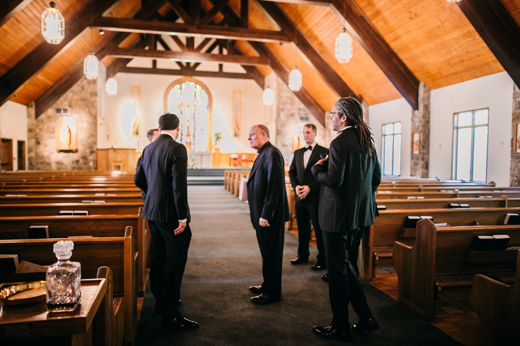 men in black tuxes stand between wooden pews under the peaked wooden roof of a church