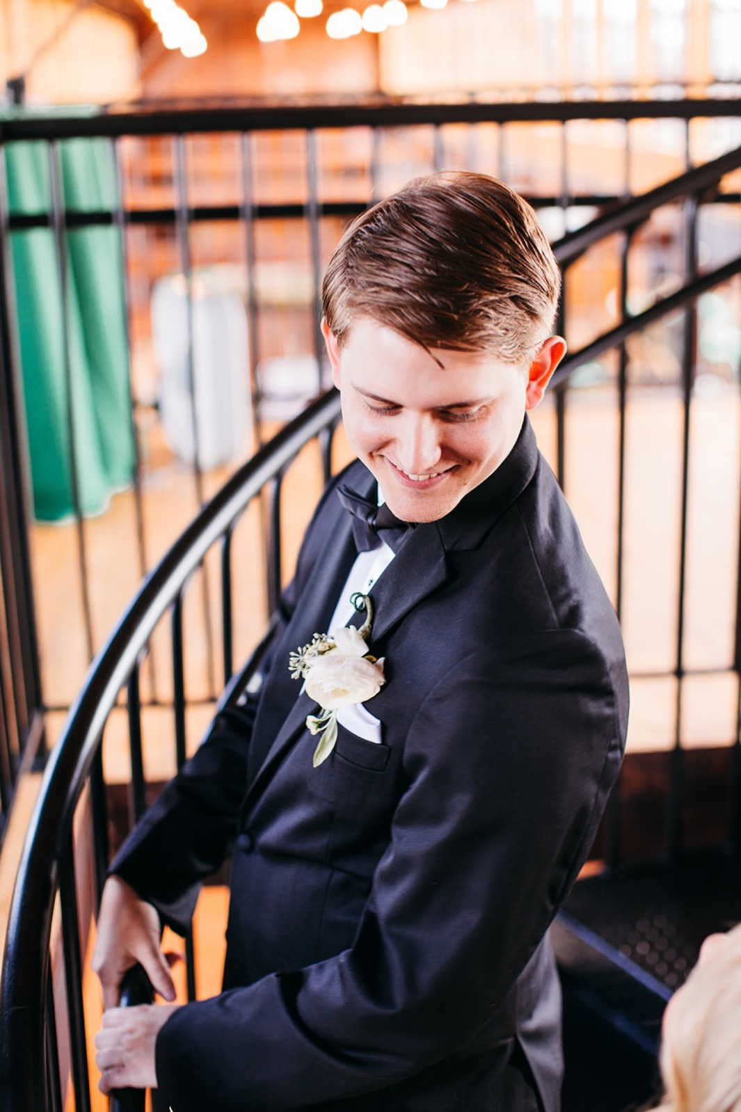 Groom smiles at the bride during the first look at their wedding in the Turnbull building.
